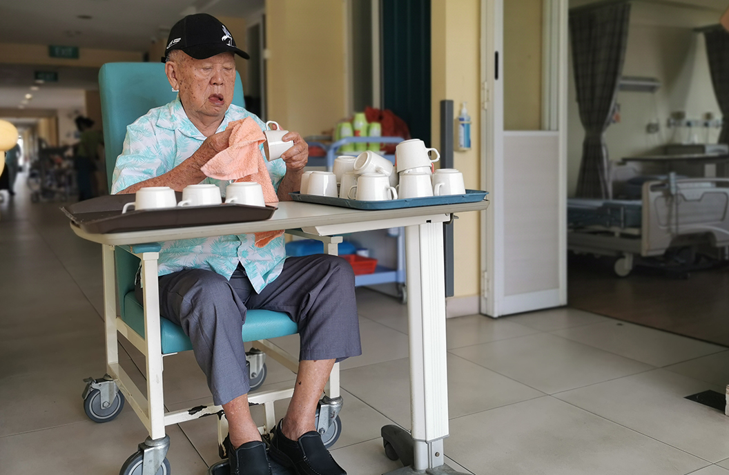 Bright Hill resident Goh Ah Huan helps with cleaning and drying cups.